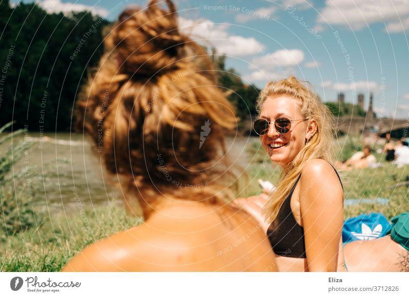 Zwei junge Frauen beim Sonnen und Baden an der Isar in München. Eine davon ist blond, trägt eine Sonnenbrille und lacht. Sommer. Freundinnen sonnen gute Laune