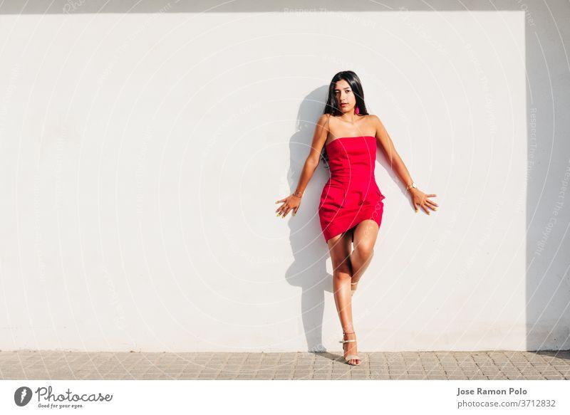 Porträt eines eleganten jungen lateinischen Mädchens mit langen brünetten Haaren und rotem Kleid an weißer Wand mit starkem Schatten, in die Kamera blickend