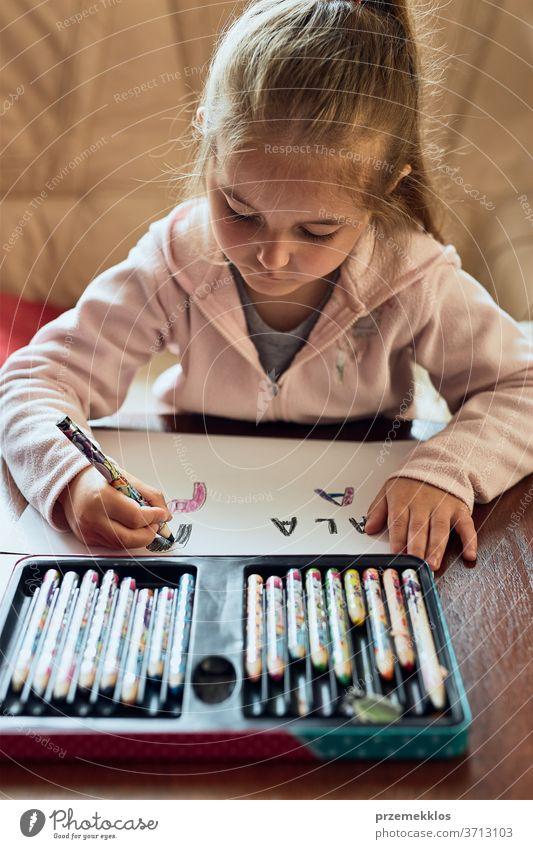 Kleines Mädchen im Vorschulalter, das zu Hause lernt, Briefe zu schreiben. Kind benutzt Buntstifte bei Hausaufgaben. Konzept der Früherziehung Aufmerksamkeit