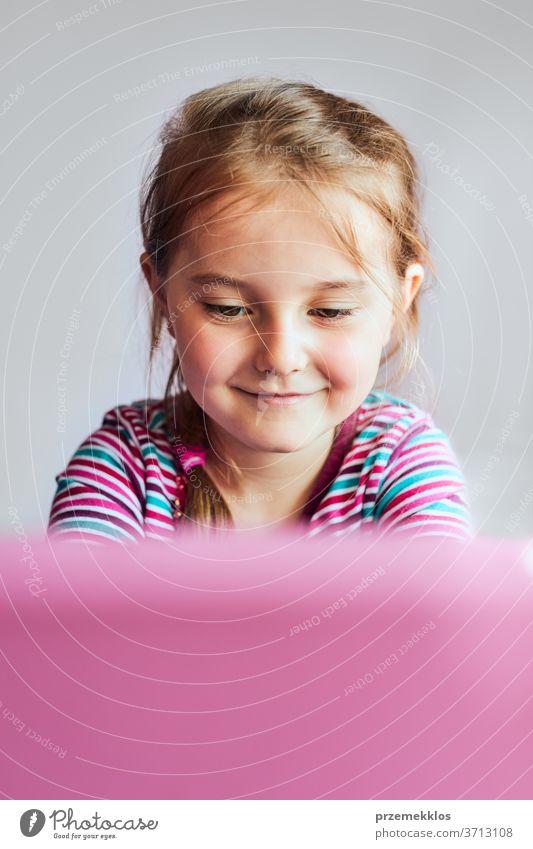 Kleines Mädchen im Vorschulalter, das online lernt, Puzzles löst und Lernspiele spielt und während der COVID-19-Quarantäne zu Tönen listet und Video auf Tablet schaut, am Schreibtisch vor dem Computer sitzt und auf den Bildschirm schaut