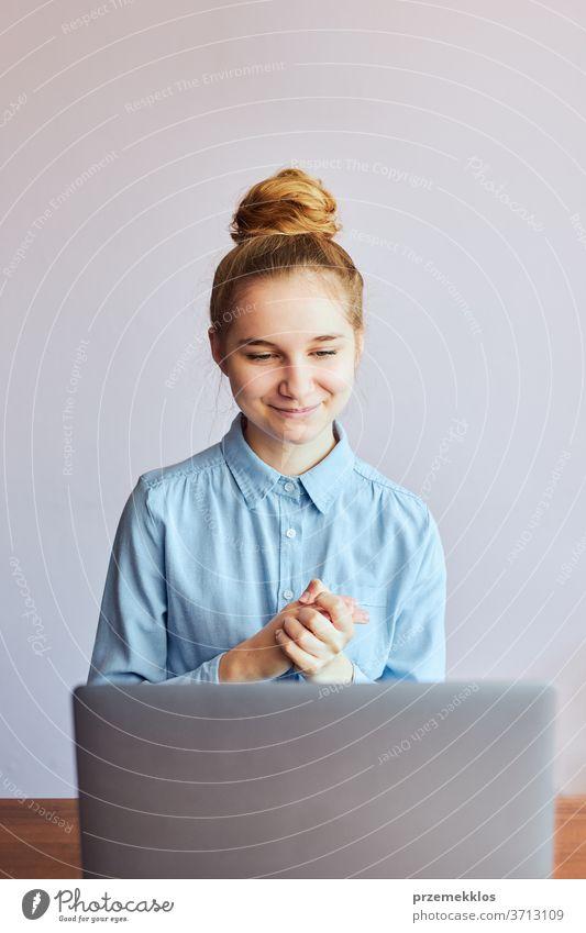 Junge Studentin, die Unterricht hat, online lernt, den Unterricht aus der Ferne verfolgt, dem Professor zuhört, während der Quarantäne von zu Hause aus per Videoanruf mit ihren Klassenkameraden spricht. Junges Mädchen mit Laptop an einem Schreibtisch sitzend