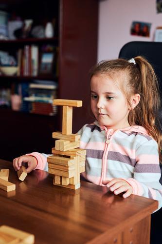 Kleines Mädchen im Vorschulalter, das mit Holzklötzchen spielt, die einen Turm bauen. Konzept für den Bau eines Hauses Kind Spielen Blöcke Spielzeug biulding