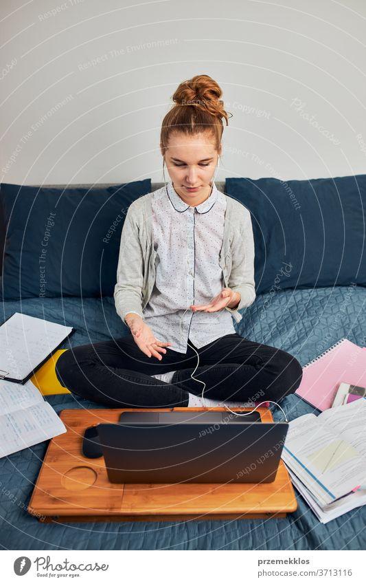 Junge Studentin, die Unterricht hat, online lernt, den Unterricht aus der Ferne verfolgt, dem Professor zuhört, während der Quarantäne von zu Hause aus per Videoanruf mit ihren Klassenkameraden spricht. Junges Mädchen benutzt Laptop, Kopfhörer, Bücher, Handbücher auf dem Bett sitzend