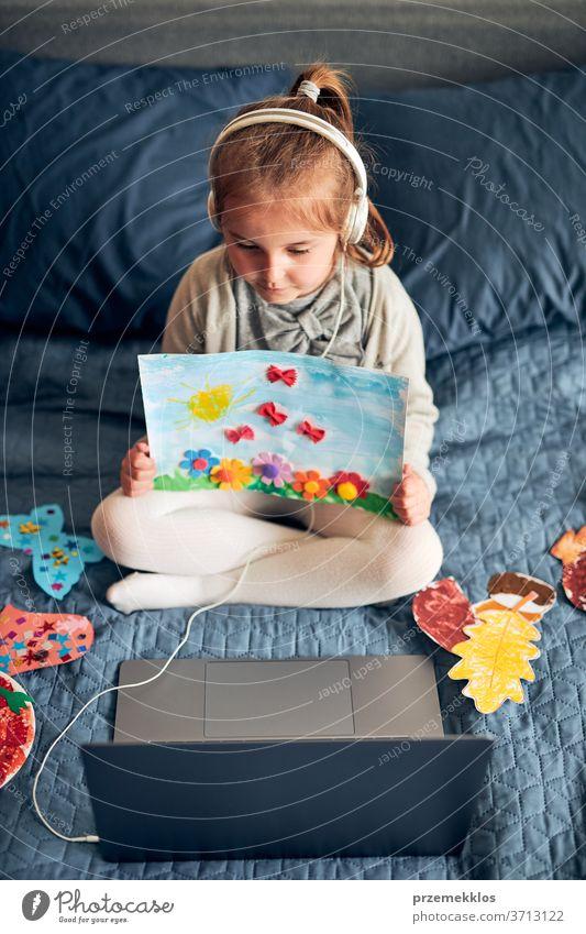 Kleines Mädchen im Vorschulalter lernt online und zeigt ihre zu Hause gezeichneten Arbeiten. Kind, das lernt, die Lektion aus der Ferne zu verfolgen und während der Quarantäne von zu Hause aus per Videoanruf mit der Tutorin zu sprechen. Kind benutzt Laptop, Kopfhörer auf dem Bett sitzend