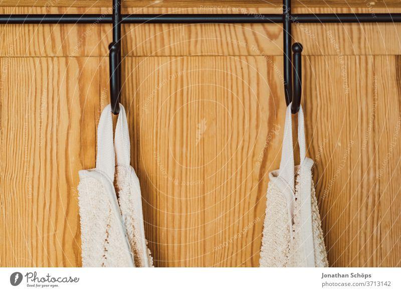 weiße Handtücher am Haken an einer Holztür Bad Badezimmer Ferienwohnung Handtuchhaken Hotel Innenaufnahme Trocknen Tür Wohnung Zuhause aufhängen ordentlich
