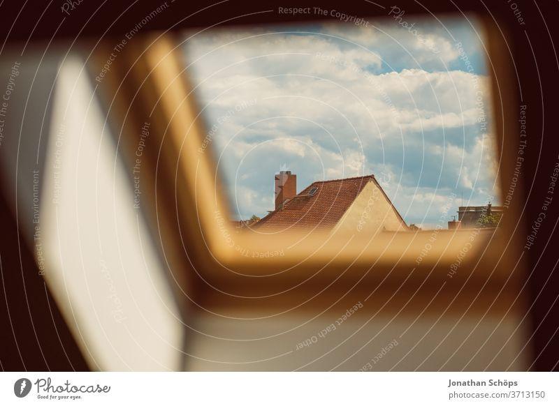 Ausblick durch ein Dachfenster auf ein Haus und Himmel Innenaufnahme Kippfenster Licht Lichteinfall Nachbar Nachbarschaft Schornstein Sonnenlicht Wohnhaus