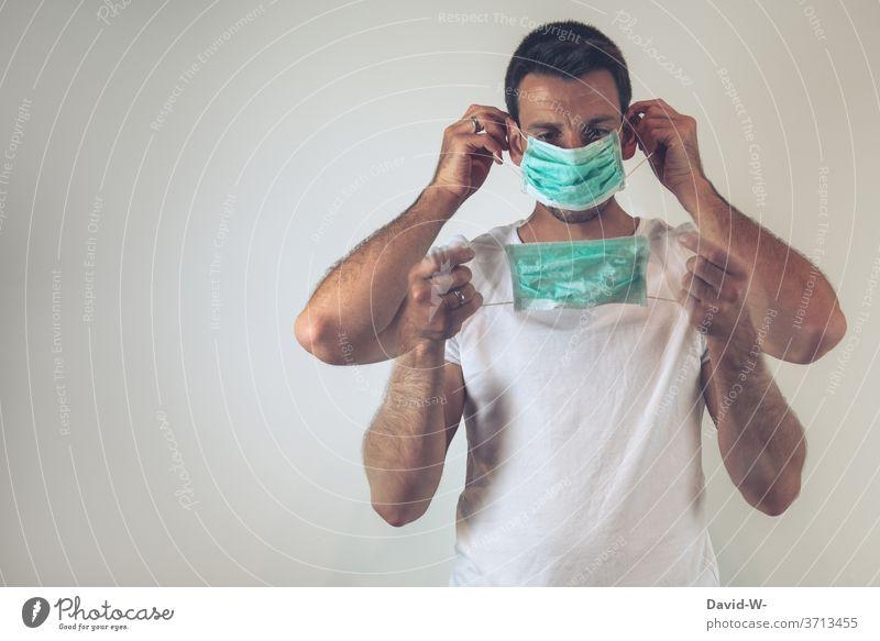 Corona - Mann setzt sich eine Atemschutzmaske / Mundschutz richtig auf aufsetzen Kontrolle Sicherheit Gesundheit Maskenpflicht Pandemie Coronavirus