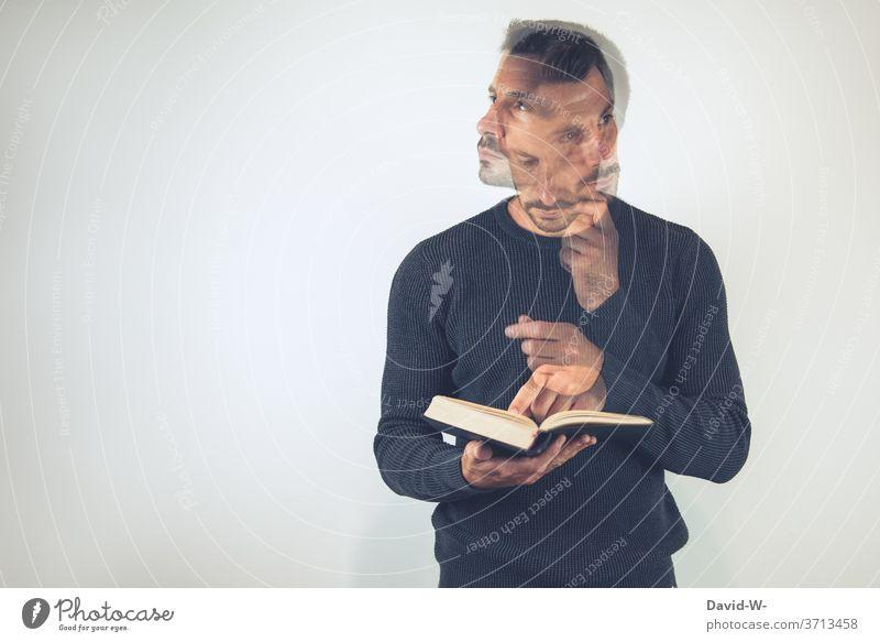 Mann hält ein Buch in den Händen und schlägt etwas nach / überlegt / denkt nach nachdenklich Bücher überlegen lesen Bildung lernen Bibliothek Wissen Schule