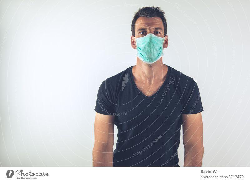 junger Mann mit Atemschutzmaske schaut in die Kamera Corona Coronavirus Pandemie Maske authentisch echt Geduld verlieren Mundschutz Virus Krankheit Gesundheit