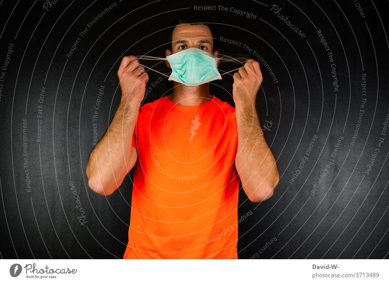 Mann hält sich eine Maske / Munschutz vor das Gesicht Corona Hände festhalten aufziehen anziehen aufsetzen testen Maskenpflicht Menschen coronavirus Coronavirus