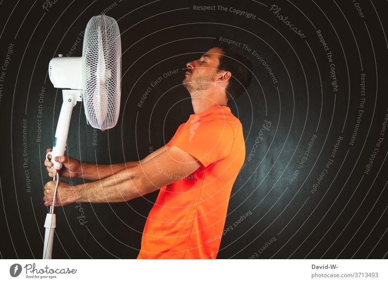 Mann hält Ventilator in den Händen hitze schwitzen warm heiß Sommer Sportler sportlich Wärme Luft