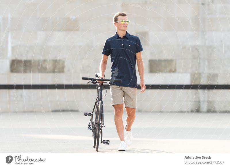Junger Mann mit Fahrrad auf der Straße Erwachsener blond lässig Kaukasier Textfreiraum Mitfahrgelegenheit Fahrradfahren Radfahrer Lifestyle männlich
