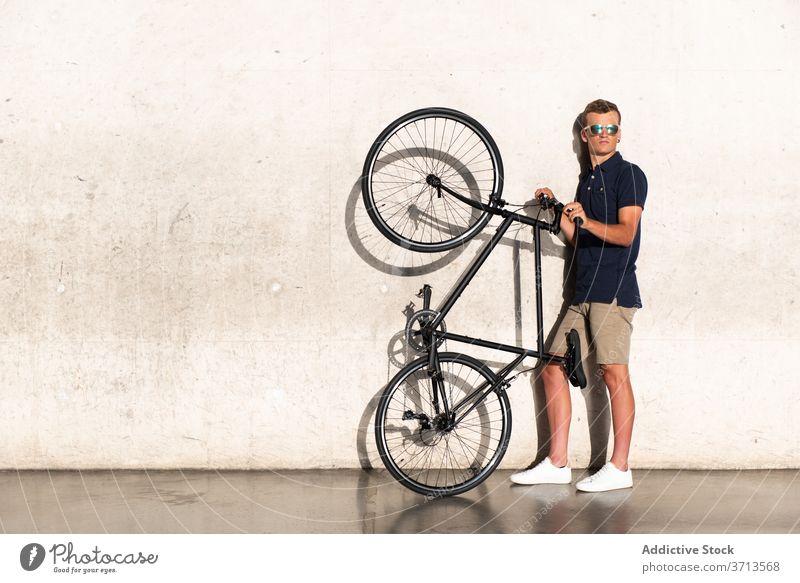 Mann trägt sein Fahrrad auf Betonwand Erwachsener blond lässig Kaukasier Fahrradfahren Radfahrer Lifestyle fettarm männlich Halt tausendjährig Mobilität modern