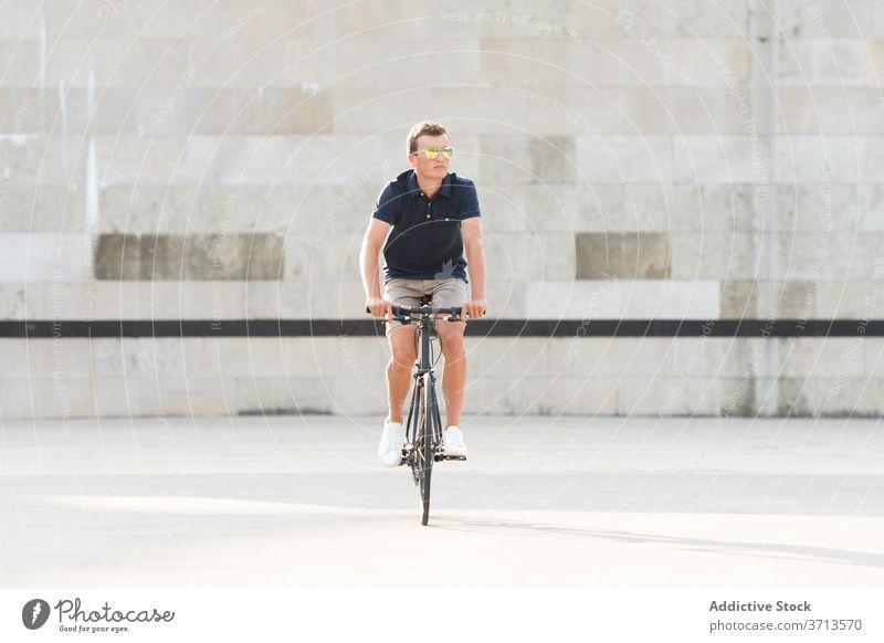 Junger Mann fährt Fahrrad auf der Straße Erwachsener blond lässig Kaukasier Textfreiraum Mitfahrgelegenheit Fahrradfahren Radfahrer Lifestyle männlich