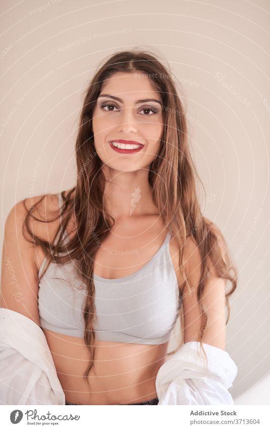 Lächelndes junges Modell mit frischem eleganten Make-up Frau Kosmetik modern heiter Inhalt feminin ethnisch brünett lange Haare rote Lippen professionell