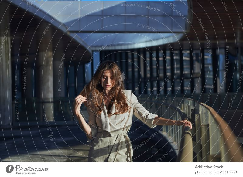 Nachdenkliche junge Frau steht in der Nähe von modernen Gebäude nachdenklich besinnlich einsam Denken urban traurig Zeitgenosse nachdenken Lifestyle träumen