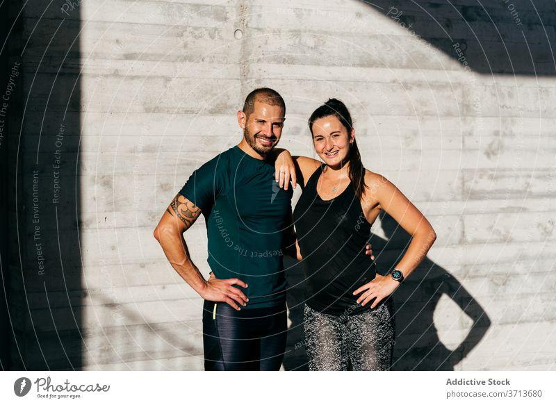 Sportliches Paar, das sich beim Training auf der Straße umarmt Umarmung sportlich Athlet Großstadt Partnerschaft Liebe Sportbekleidung Lächeln Fitness Glück