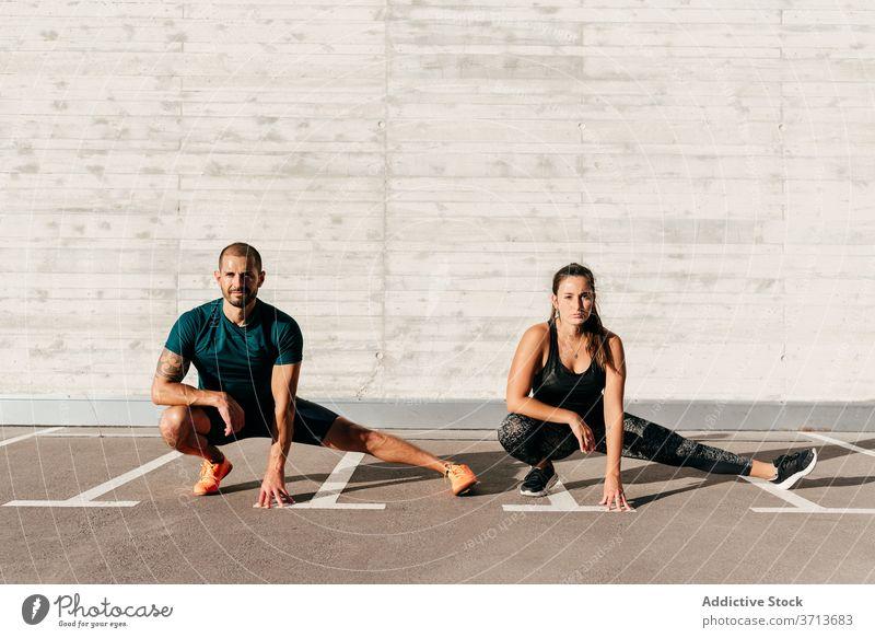 Fit-Sportler trainieren auf der Straße Seitenlonge Training Paar Partnerschaft Gesundheit Athlet Fitness Übung Zusammensein Sportbekleidung Wellness sonnig