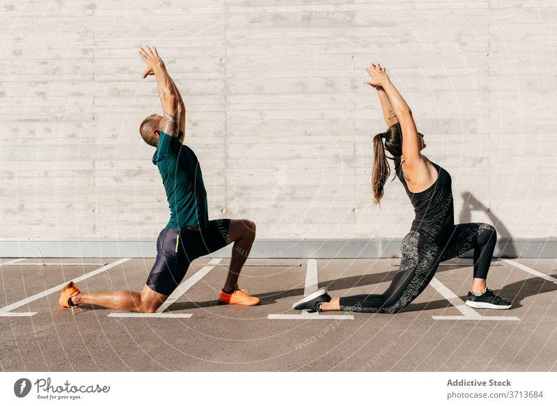 Fit Paar tun Yoga zusammen in der Stadt Sichel-Lungen-Pose Zusammensein üben Asana anjaneyasana Sportbekleidung meditieren Gesundheit Harmonie Wellness