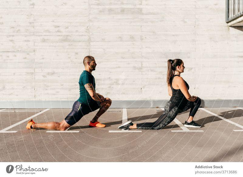 Sportliches Paar beim Aufwärmen vor dem Training Dehnung Körper Zusammensein Athlet beweglich Sportbekleidung Gesundheit Aktivität Wohlbefinden stehen