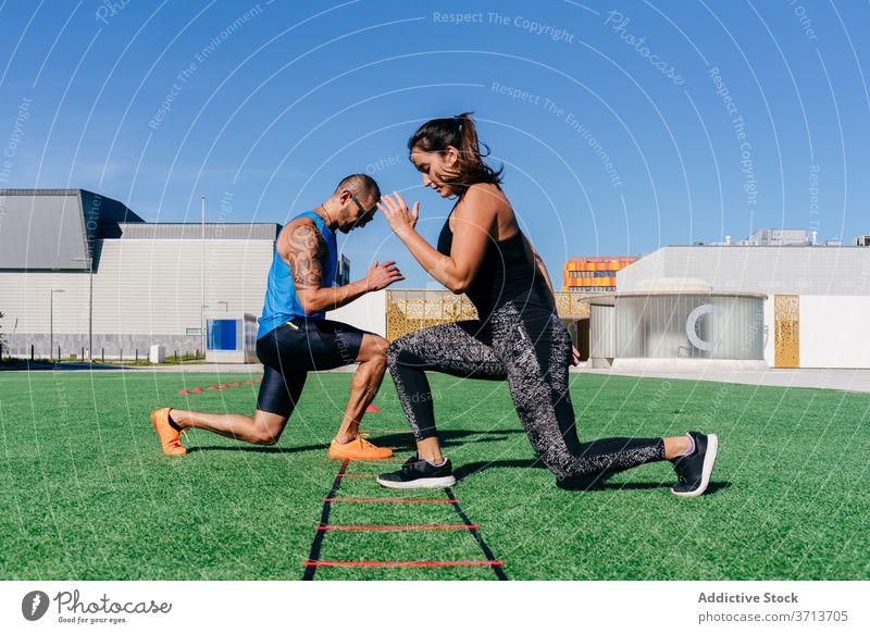 Athletisches Paar beim Training mit der Agility-Leiter auf dem Sportplatz Laufmasche Beweglichkeit Übung Gerät Ausfallschritt Zusammensein Fitness passen
