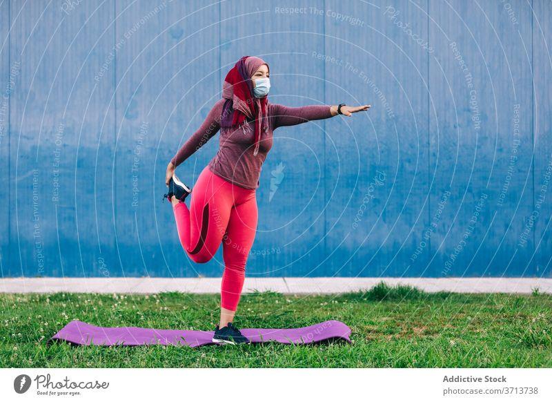 Frau beim Training im Park Aufwärmen Dehnung Sportlerin Hijab muslimisch Unterlage Athlet ethnisch arabisch medizinisch Mundschutz behüten Coronavirus COVID