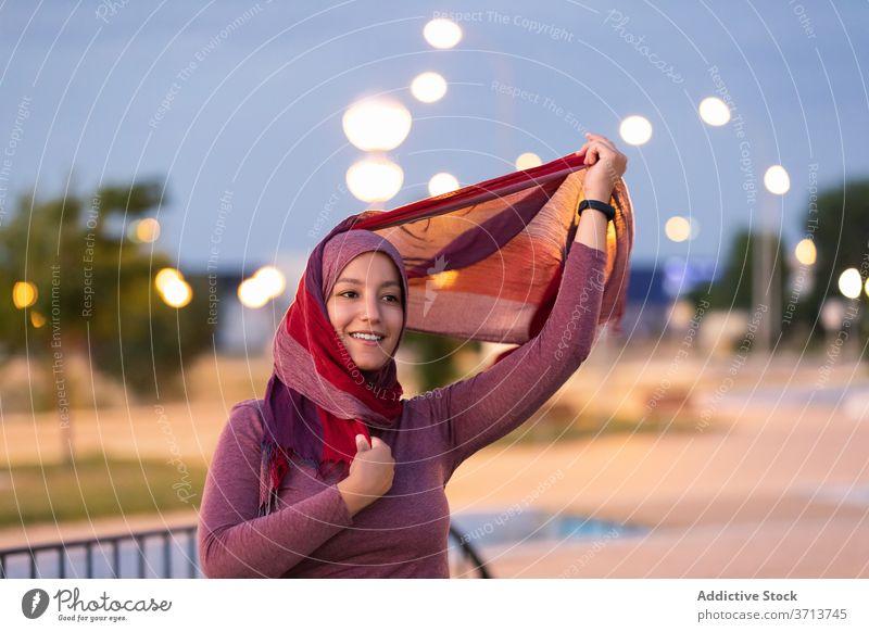 Lächelnde arabische Frau im Hidschab auf der Straße Hijab angezogen muslimisch religiös Großstadt Abend Kopfschmuck Inhalt ethnisch Glück Stil froh Freude