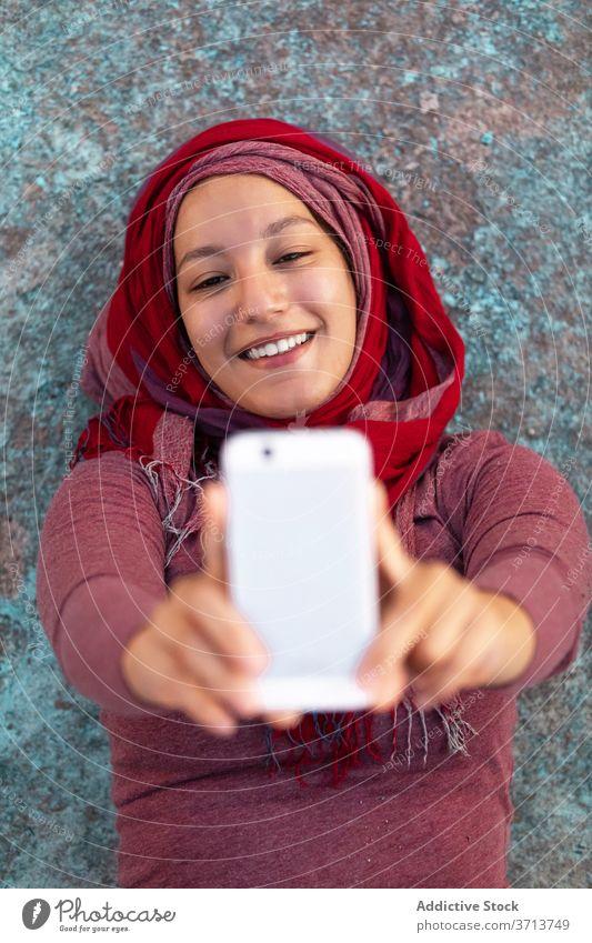 Glückliche Frau nimmt Selfie mit Handy auf der Straße Großstadt benutzend Smartphone Hijab Lächeln heiter arabisch ethnisch Gebäude Browsen Funktelefon online