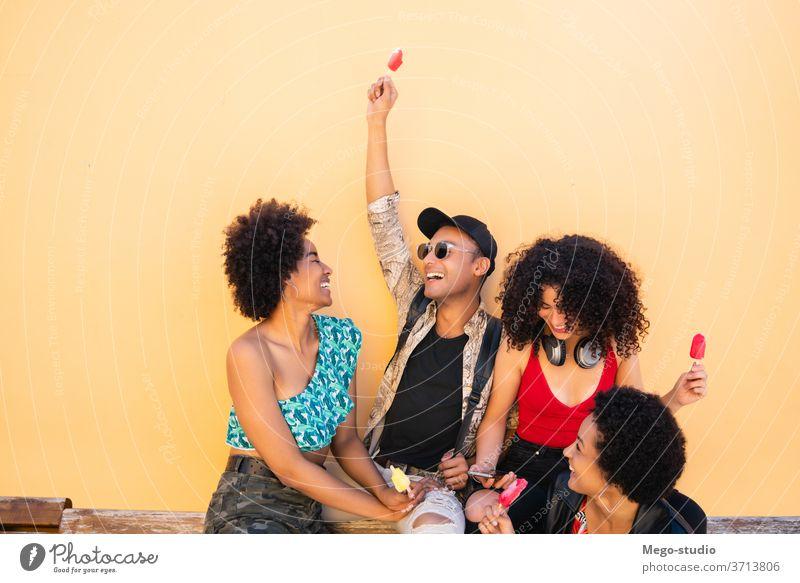 Eine multiethnische Gruppe von Freunden genießt die Sommerzeit beim Eisessen. Freundschaft jung Menschen Dessert Essen Vielfalt vielfältig genießen Vergnügen