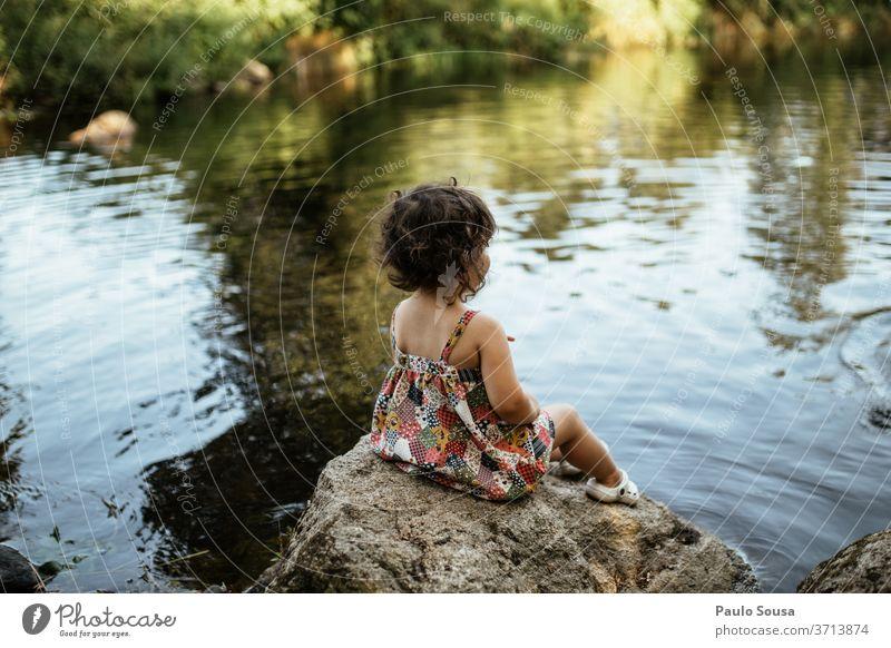 Kind am Flussufer sitzend Kindheit Kindheitserinnerung Mensch Sommer Freude Freizeit & Hobby Farbfoto Kleinkind Spielen Außenaufnahme reisen Lifestyle