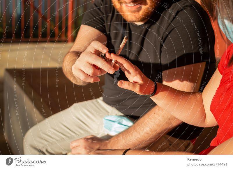 Junges Paar, das sich während eines Sonnenuntergangs auf der Straße einen Marihuana-Laden teilt. Gelenk Topf Cannabis Rauch Glück Lächeln Teilen Freunde Mann