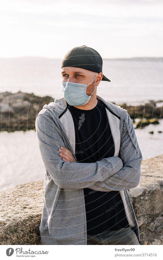 Tourist mit einer chirurgischen Maske in Meeresnähe Porträt Mann Operationsmaske Küste Strand reisen Tourismus Reisender Mundschutz Pandemie Coronavirus COVID19