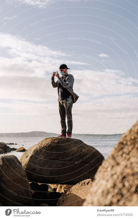 Tourist mit Gesichtsmaske fotografiert mit seinem Smartphone Fotografieren Küste Felsen Strand Meer Porträt Mann Operationsmaske reisen Tourismus Reisender