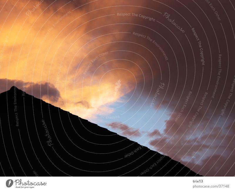 hausdach im Sonnenuntergang Dach Wolken schwarz gelb violett Abenddämmerung Himmel orange blau Strukturen & Formen Wetter