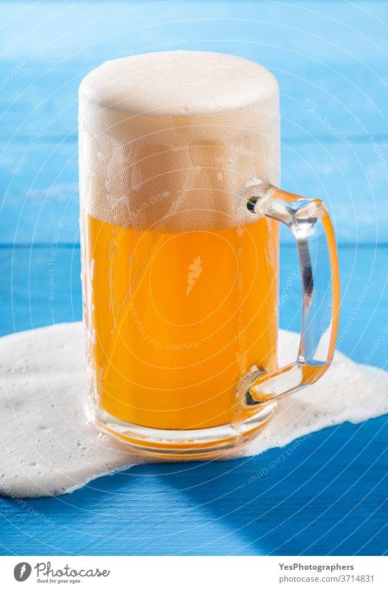 Ein Pint Bier mit verschüttetem Schaum auf blauem Tisch. Deutsches unfiltriertes Bier Oktoberfest Unfall Alkohol Hintergrund Bar bayerisch Bierschaum Getränk