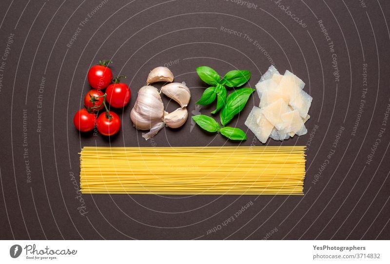 Spaghetti und die Saucenzutaten, Draufsicht. Ungekochte Nudeln isoliert braun gefärbten Tisch. obere Ansicht ausgerichtet Hintergrund Basilikum Kohlenhydrat