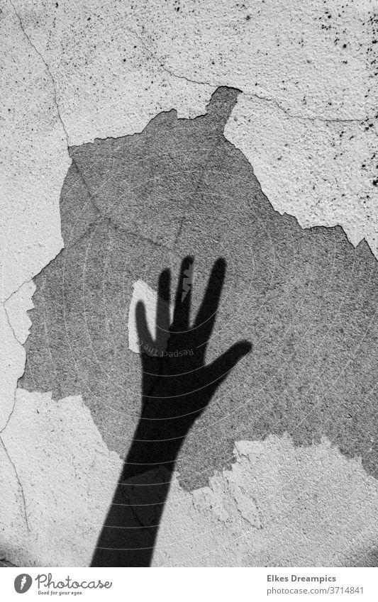 Schatten einer Hand an einer alten Wand schattenbilder Risse