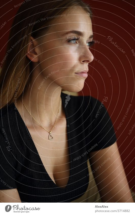 Seitliches Portrait einer jungen Frau vor roter Wand sportlich feminin Empathie Gefühle emotional Porträt Zentralperspektive Schwache Tiefenschärfe