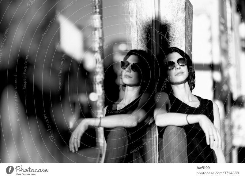 die junge Frau genießt entspannt die Morgensonne Junge Frau Porträt brünett Blick in die Kamera 1 Sonnenbrille hübsch Beautyfotografie Schwarzweißfoto natürlich