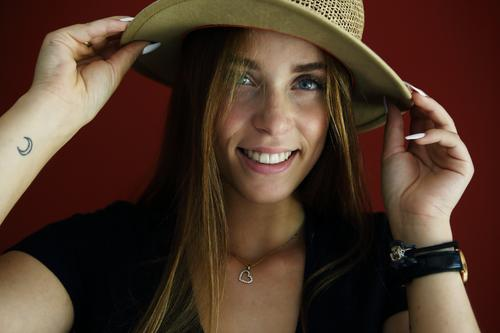 Direktes Portrait einer jungen Frau vor roter Wand mit einem Strohhut sportlich feminin Empathie Gefühle emotional Porträt Zentralperspektive