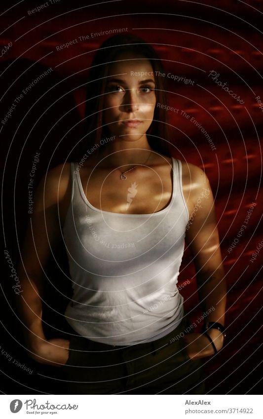 Portrait einer jungen Frau in Lichtstreifen von Jalousie vor roter Wand Licht und Schatten sportlich feminin Empathie Gefühle emotional Blick in die Kamera