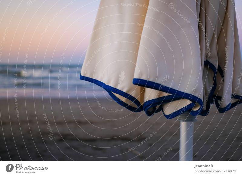 geschlossener Sonnenschirm mit Abendstimmung blau Ferien & Urlaub & Reisen Meer Erholung Sommerurlaub Strand Außenaufnahme Menschenleer Sonnenbad Tourismus