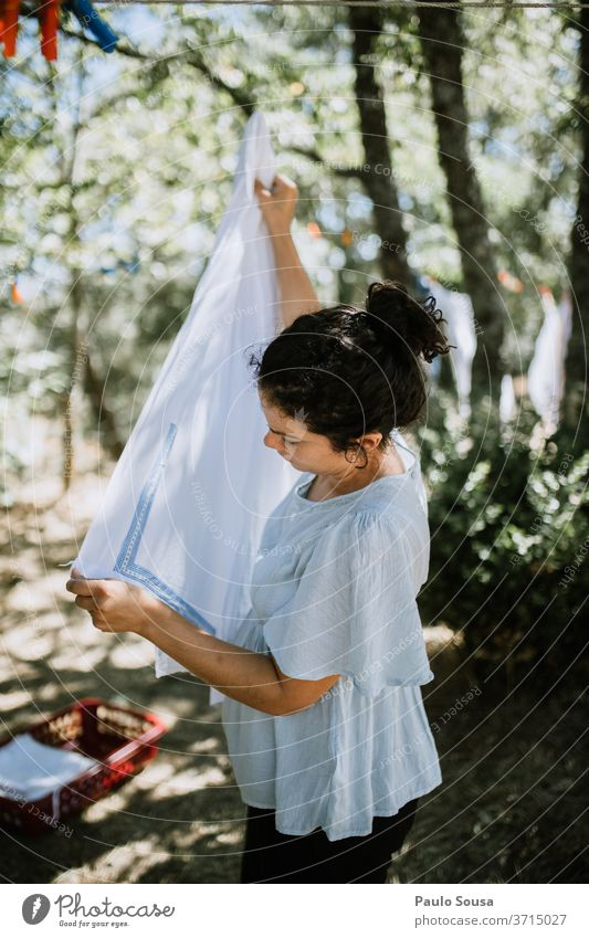 Frau hängt Kleidung an Wäscheleine Bekleidung Kleiderhaken heimisch häusliches Leben Hausfrau Hausarbeit Haushaltsführung aufhängen Waschtag Farbfoto Sauberkeit