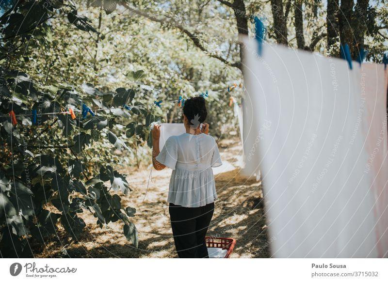 Frau hängt Kleidung an Wäscheleine Waschen Bekleidung Kleiderhaken Außenaufnahme Wäsche waschen Haushaltsführung Farbfoto trocknen Sauberkeit hängen Wäscherei