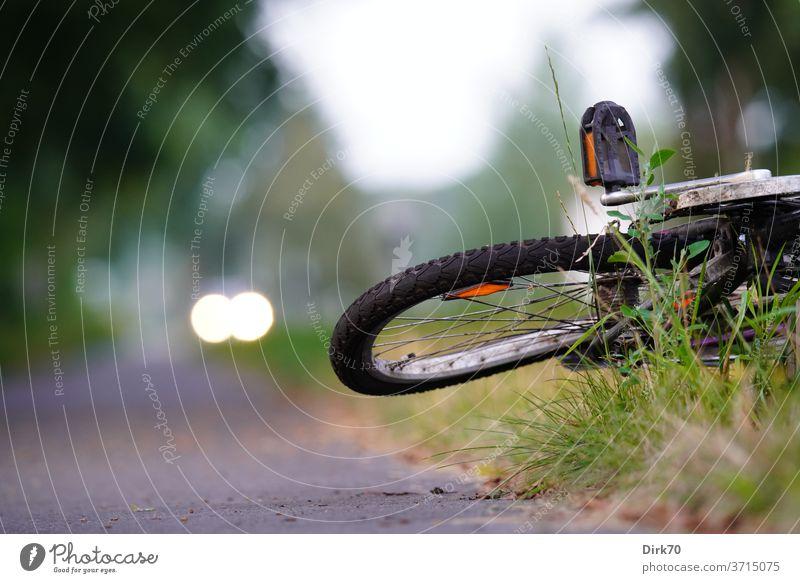 Sicherheit im Straßenverkehr - verbogenes Fahrrad am Straßenrand Verkehr Verkehrswege Unfall Rad kaputt verzogen Radweg Licht Auto Scheinwerfer