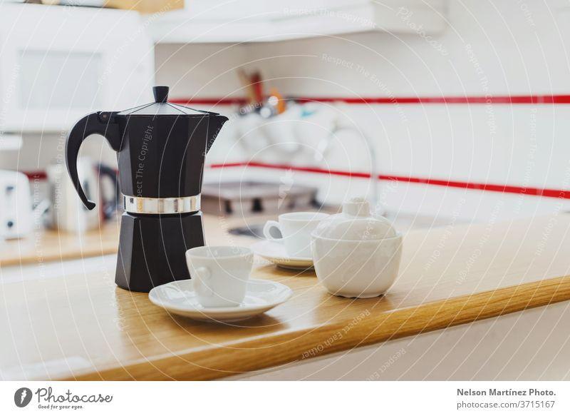 Schwarze Kaffeekanne mit weißen Tassen und einer Zuckerdose in der Küche. Kaffeemaschine in der Küche. Topf Haus Servieren Heißgetränk warm Wochenende Objekt