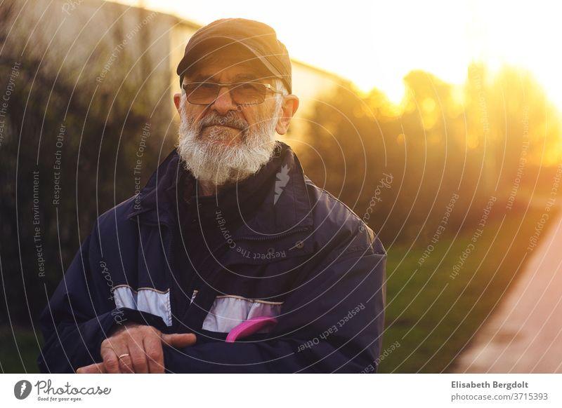 Portrait eines 75 Jahre alten Mannes mit Brille und Bart, draußen, bei Sonnenuntergang älterer mann Porträt Senior Spaziergang Männlicher Senior 60 und älter