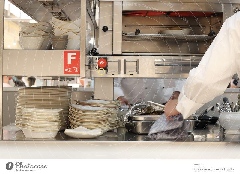 Großküche Küche Restaurant Beruf Gastronomie Teller Geschirr Durchreiche Salamander Koch Küchenchef Mann Essen zubereiten Lebensmittel Edelstahl Bestellung