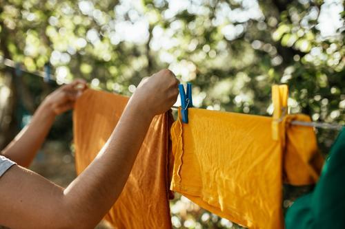 Frau hängt Kleidung an Wäscheleine Bekleidung erhängen trocknen Wäscherei gewaschen Sauberkeit Klammer Haushaltsführung Seil Außenaufnahme Waschtag