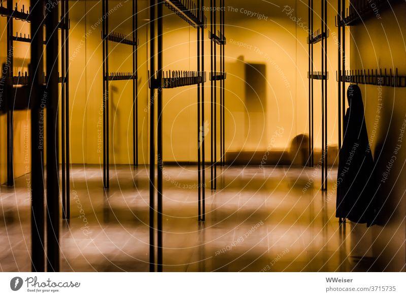 Das Konzert ist längst vorbei, eine Jacke wurde noch nicht aus der Garderobe abgeholt gelb leer Konzerthaus Theater Licht Abend vergessen letztes
